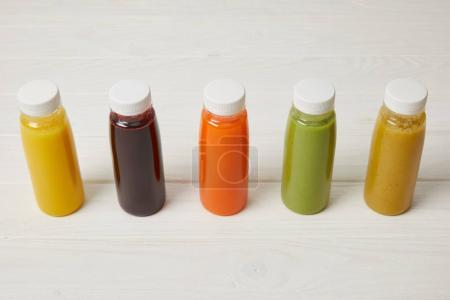fresh organic smoothies in bottles standing in row on white
