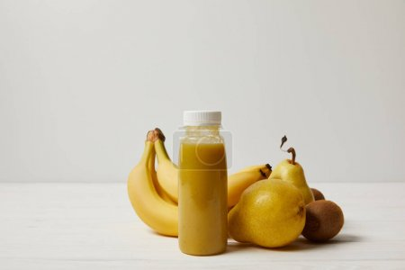 yellow smoothie with bananas, kiwis and pears on white background
