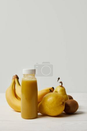 yellow detox smoothie in bottle with bananas, kiwis and pears on white background