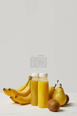 bottles with yellow smoothies with bananas, pears and kiwis on white background