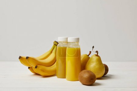 yellow detox smoothies in bottles with bananas, pears and kiwis on white background