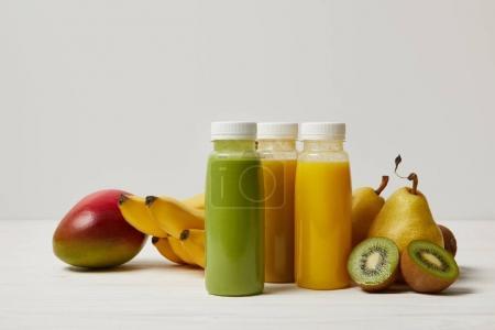 des fruits et des smoothies frais dans des bouteilles sur fond blanc