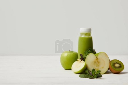green detox smoothie with apples, kiwi and mint and on white wooden surface