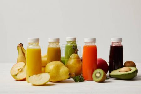 fresh fruits and detox smoothies in bottles on white wooden surface