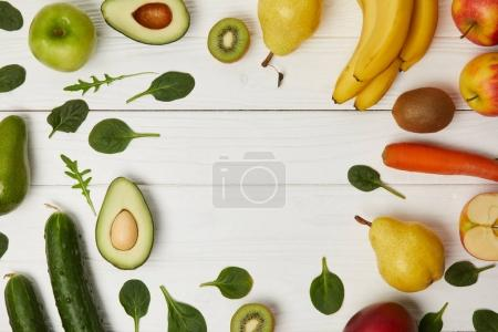 top view of fruits and vegetables on wooden background with copy space