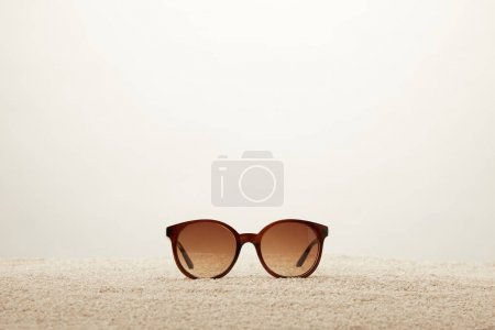 close up view of sunglasses on sand on grey background