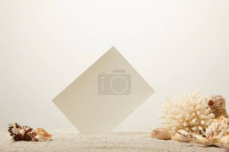 close up view of coral, seashells and blank card on sand on grey background