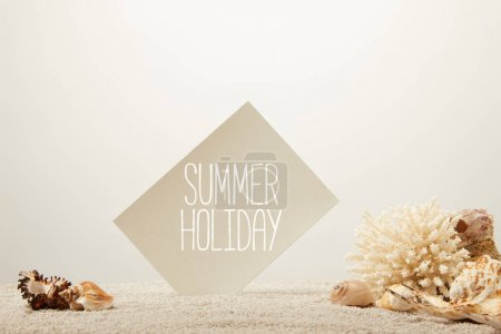 close up view of coral, seashells and card with summer holiday lettering on sand on grey background