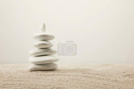 close up view of arranged white sea stones on sand on grey background