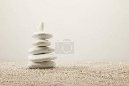 Photo pour Vue rapprochée de pierres de mer blanches disposées sur sable sur fond gris - image libre de droit