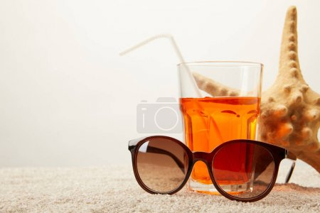 close up view of sunglasses, cocktail with straw and sea star on sand on grey backdrop