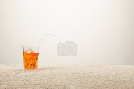 Photo for Close up view of refreshing cocktail with ice and straw on sand on grey background - Royalty Free Image