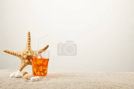 Photo for Close up view of sea star, refreshing cocktail with straw and seashells on sand on grey background - Royalty Free Image