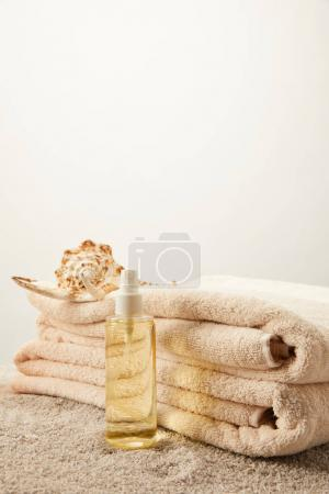 close up view of arranged pile of towels, seashell and tanning oil on sand on grey backdrop