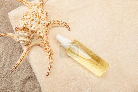 vue de dessus d'arrangé tas de serviettes, coquillage et huile de bronzage sur le sable