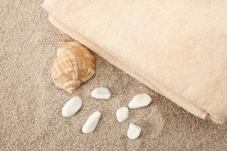 Photo pour Vue de dessus de coquillage, pierres de mer et serviettes sur sable - image libre de droit