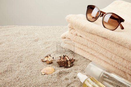 close up view of stack of towels, sunglasses, tanning oil and seashells on sand on grey background