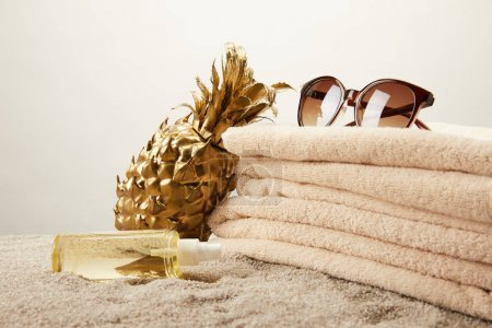 close up view of stack of towels, sunglasses, tanning oil and golden decorative pineapple on sand on grey backdrop