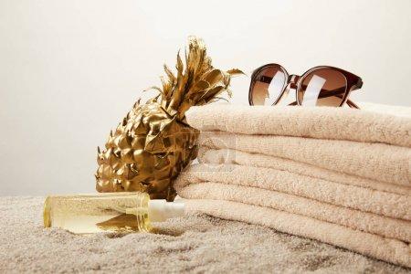 bouchent la vue de pile de serviettes de bain, lunettes de soleil, bronzage huile et or ananas décoratifs sur le sable sur fond gris