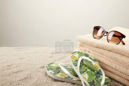Photo for Close up view of stack of towels, sunglasses and summer flip flops on sand on grey backdrop - Royalty Free Image