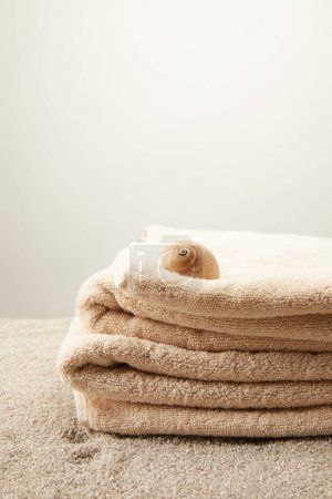 close up view of pile of towels with seashell on sand on grey backdrop