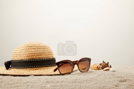 Photo for Close up view of straw hat, sunglasses and seashells on sand on grey backdrop - Royalty Free Image