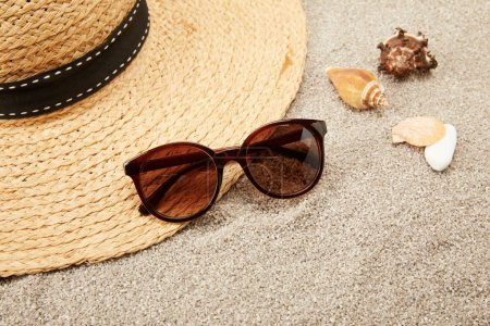 Photo for Close up view of straw hat, seashells and sunglasses on sand - Royalty Free Image