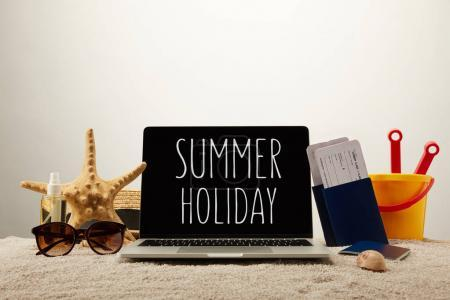 close up view of laptop with summer holiday lettering, sea star, sunglasses, passports with tickets and toy bucket on sand on grey background