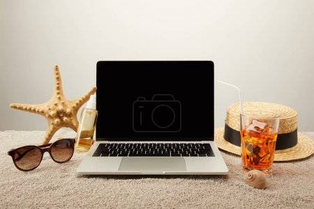 close up view of laptop with blank screen, refreshing cocktail and summer holiday accessories on sand on grey background