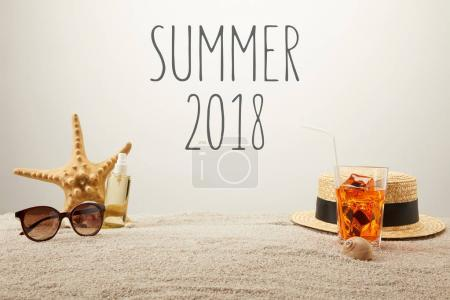 close up view of summer 2018 lettering, cocktail with ice, straw hat, sunglasses and tanning oil on sand on grey backdrop