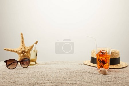 close up view of cocktail with ice, straw hat, sunglasses and tanning oil on sand on grey backdrop