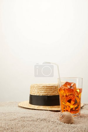 close up view of straw hat and refreshing cocktail with ice on sand on grey backdrop