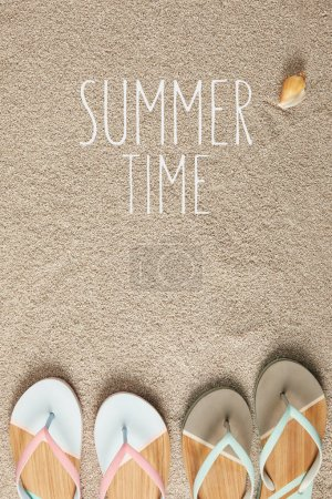flat lay with summertime lettering, flip flops and seashell on sand