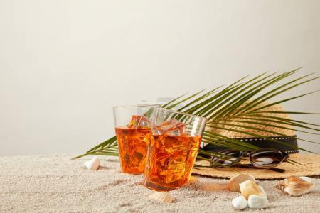 Photo pour Vue rapprochée du chapeau de paille, des cocktails, des coquillages, des lunettes de soleil et des feuilles de palmier sur fond de sable gris - image libre de droit