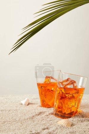 Photo pour Vue rapprochée des cocktails avec glace à la feuille de palmier et coquillages sur sable sur fond gris - image libre de droit