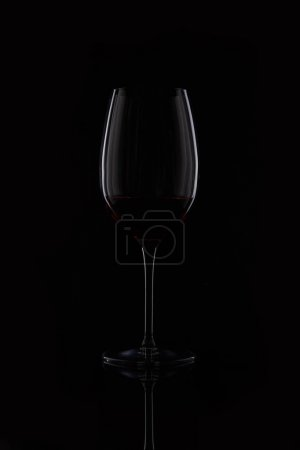 closeup shot of glass with red wine isolated on black background