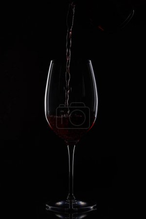 closeup shot of red wine pouring into glass from bottle isolated on black background