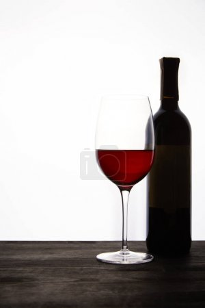 closeup view of bottle and glass with red wine on dark wooden table