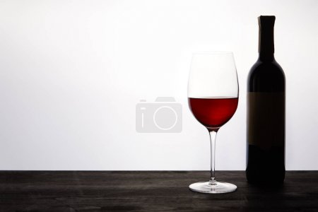 bottle and glass with red wine on dark wooden table
