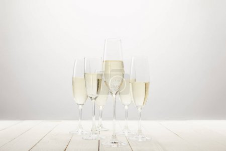 Photo for Closeup view of champagne glasses on white wooden table - Royalty Free Image
