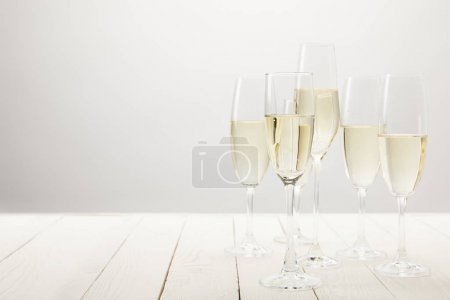 closeup shot of champagne glasses on white wooden table