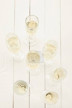 top view of champagne glasses on white wooden table