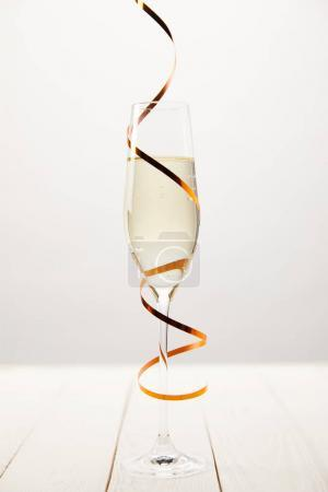 Closeup view of champagne glass wrapped by serpentine on white wooden table, holiday concept