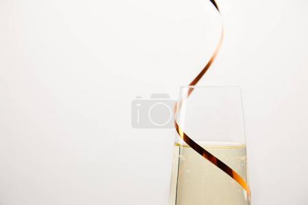 close up shot of champagne glass wrapped by ribbon isolated on white background, holiday concept