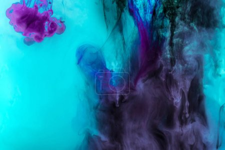 creative texture with turquoise and purple swirls of paint in water