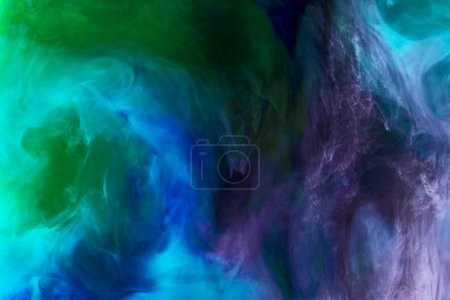 creative background with purple, blue and green watercolor paint in water as space