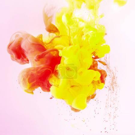 Photo pour Texture avec des remous de peinture jaune et rouge qui coule sur rose - image libre de droit