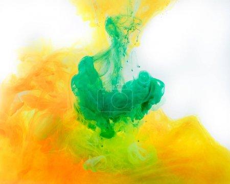 Photo pour Fond fumé avec de la peinture verte et orange coulant dans l'eau - image libre de droit