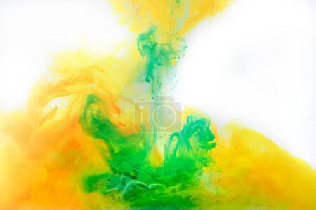 abstract background with green and orange paint swirling in water