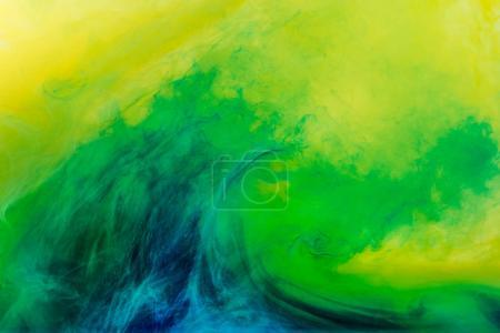 abstract background with green paint flowing in yellow water